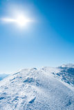 Snowy mountains with the sun Stock Image
