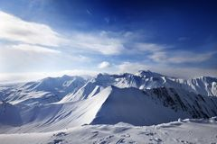Snowy mountains and sunlight sky Stock Image