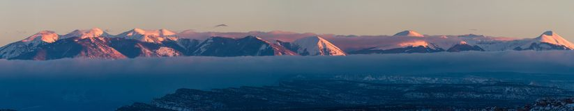 Snowy mountains at sunset. La sal mountain panorama ar sunset with a dense for at the base of the mountains and clear skies above them stock image