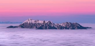 Snowy mountains tops covered in clouds with beautiful pink sky stock photography