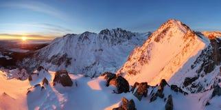 Snowy mountains under orange sunset sky.  Royalty Free Stock Photo