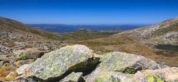 Snowy mountains view. Landscape near Mt Kosciuszko with lichen covered ganite in the foreground Royalty Free Stock Photography