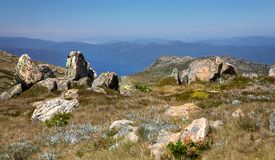 Snowy mountains view. Landscape near Mt Kosciuszko with lichen covered ganite in the foreground Stock Images