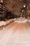 Snowy-Nachtbahn in der Stadt Helles Licht von Laternen vertikal Stockfoto