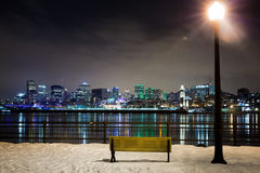 A snowy night in Montreal. A winter night in Montreal. Park bench and street light with the St Lawrence river and downtown Montreal in the background Royalty Free Stock Photography