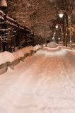 Snowy night pathway in city. Bright light of lanterns. Vertical Stock Photo