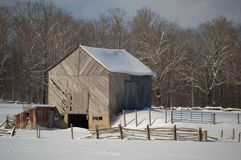 Snowy old barn with diagonal boards and barnyard. Snowy old barn on a sunny day. Barnboards run diagonally and are grey, old and weathered. Shows some fence and stock image