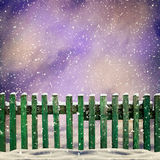 Snowy old green wooden fence and falling snow Stock Image