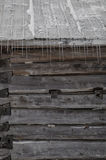 Snowy old log cabin barn with icicles background Stock Photography