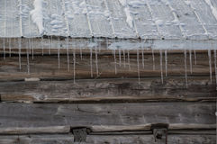 Snowy old log cabin barn with icicles background Royalty Free Stock Images