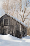 Snowy old log cabin barn with icicles Stock Image
