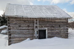 Snowy old log cabin barn with icicles Royalty Free Stock Photography