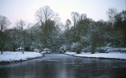Snowy park. Frozen ditch in a snowy park royalty free stock photography