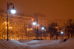 Snowy park in the evening. A park covered in snow lit by evening lights Royalty Free Stock Photo