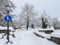 Snowy park with footpath and traffic sign for pedestrians. Snowy park in winter with traffic sign in Germany stock photography