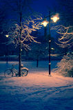 Snowy park lighted at night. Street lamps illuminating snowy city park at night with bicycle leaning against post; winter scene.  Location: Tampere, Finland Stock Photo