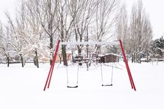 Snowy park with swings and trees Stock Images