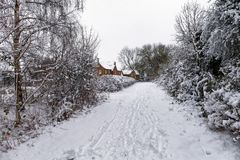 Snowy path through the park. With buildings in the background Stock Photos