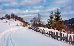 Snowy path through rural area in mountains. Lovely countryside scenery of wooden fence and naked trees Royalty Free Stock Photography