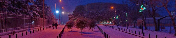 Snowy pathway and street lights. A picture of a snowy pathway in a srreet of trees and street lights in the corner,in a snowy day afternoon,in a town in Greece Stock Photo