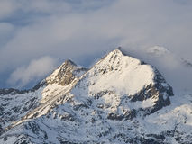 Snowy Peak. Summit of a snowy mountain surrounded by clouds Stock Photography