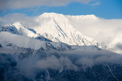 Snowy Peak. A snowy peak peeps out from behind wispy white clouds Stock Photography