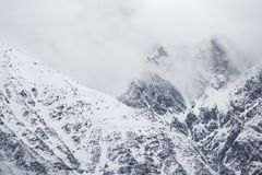 Snowy peak in the clouds royalty free stock photo