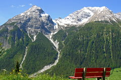 Snowy peaks and a bench. To relax Royalty Free Stock Photos