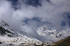 Snowy peaks in the clouds. Trekking to Annapurna Base Camp. Nepal stock photo