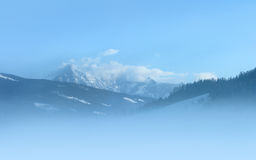 Snowy peaks at foggy morning. Royalty Free Stock Photo