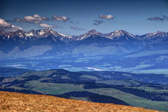 Snowy peaks and green hills in Western Tatras, Liptov, Slovakia. Snowy peaks and saddles of Western Tatras and green hills of Vah valley in Liptov region, in a Stock Image