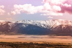 Snowy peaks of the mountain range under the pink sky. Mountain landscape in pastel color stock photos