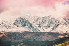Snowy peaks of the mountain range under the pink sky. Mountain landscape in pastel color stock image