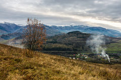 Snowy peaks over rural area in autumn. High mountains snowy peaks over rural area in autumn under the cloudy sky Stock Photo