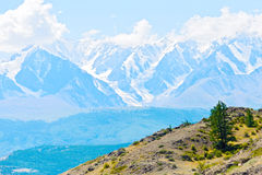 Snowy peaks. Snow-capped mountain peaks with a striking blue hue. Away the clouds and sky Royalty Free Stock Image