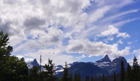 Snowy Peaks and Summer Skies, Glacier National Park. Lofty peaks with lingering snow scrape the passing clouds in a bright blue Summer sky. This is the view from royalty free stock image