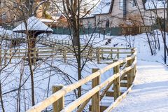 Snowy Photo of the Park on a Sunny Winter day - Wooden Footpath in the Middle of it, Concept of the Harmony and Travel. In the Countryside stock photos