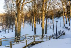 Snowy Photo of the Park on a Sunny Winter day - Wooden Footpath in the Middle of it, Concept of the Harmony and Travel. In the Countryside stock image
