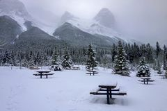 Snowy Picnic Area Cold Winter Country Canmore Alberta Canada. Snowy Picnic Area and Winter Landscape with Distant Rocky Mountain Tops obscured by Clouds above royalty free stock photo