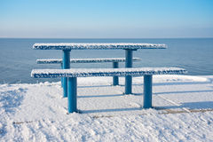 Snowy picnic table and bench along dutch coast. Wintertime at the of the Noordoostpolder. The picnic table is somewhat cold stock images