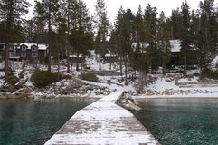Snowy Pier. Dock at Lake Tahoe coming straight out from shoreline with cabins in background stock photos