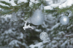 Snowy pine tree branches with sparkling reindeer ornament and Christmas baubles at wood background Stock Photos