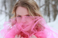 Snowy Pink Winter Woman Portrait. An beautiful young woman peering through bright pink tulle in a snowy forest Royalty Free Stock Image