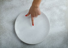 Snowy plate background with a woman hand Stock Photo