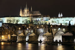 Snowy Prague Castle with Charles Bridge in Night Stock Photo