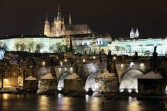 Snowy Prague Castle With Charles Bridge In Night Stock Photo