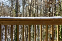 Snowy Railing with Trees in the Background royalty free stock image