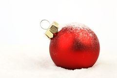Snowy red christmas matt ball standing on snow on white background Stock Photography