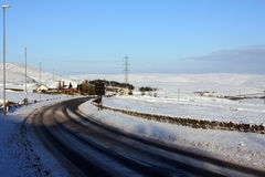 Snowy road bend in a hilly countryside Stock Images
