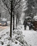 Snowy road during a big snowfall in the city with some pedestria royalty free stock photo